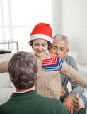 Son In Santa Hat About To Embrace Father. Smiling son in Santa hat about to embrace father with senior men in background at home Stock Image