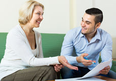 Son and senior mother with documents. Happy smiling adult son helping mature mother with financial documents stock photography