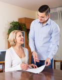 Son and senior mother with documents. Son helping smiling senior mother with documents for buying apartment royalty free stock images