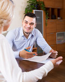 Son and senior mother with documents. Smiling adult son helping aged mother with documents for buying apartment at the table royalty free stock images