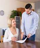 Son and senior mother with documents. Smiling adult son helping senior mother with documents for buying apartment royalty free stock photography