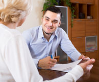 Son and senior mother with documents. Smiling adult son helping mature mother with financial documents at the table stock photo