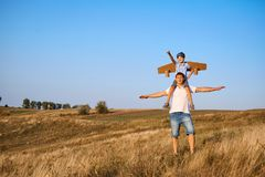 Son on the shoulders of his father in the open air in the field Stock Images