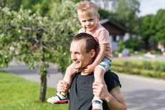 Son on the shoulders of his father rk. Son on the shoulders of his father in the park Royalty Free Stock Images