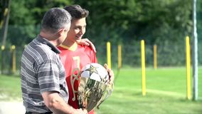 Son showing dad winning soccer trophy and waving stock video footage