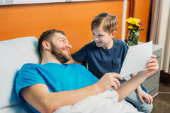 Son showing sick father his drawings at ward, hospital patient care. Little son showing sick father his drawings at ward, hospital patient care royalty free stock photography