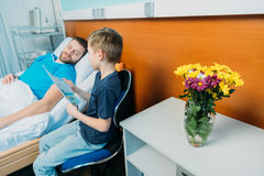 Son showing sick father his drawings at ward, hospital patient care. Little son showing sick father his drawings at ward, hospital patient care royalty free stock image