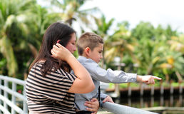 Son showing something to his mother. Young boy pointing and showing something to his mother outdoors Stock Image