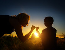 Son shows temper of mother. At sunset Royalty Free Stock Photos