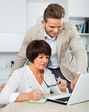 Son shows to his elderly mother new software on laptop. Loving  son shows to his elderly mother new software on laptop Royalty Free Stock Photos