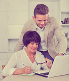 Son shows to his elderly mother new software on laptop. Loving positive  son shows to his elderly mother new software on laptop Royalty Free Stock Photos