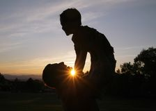 Son Silhouette. Silhouette of a father holding son in the air and smiling at sunset with sun showing Stock Photography