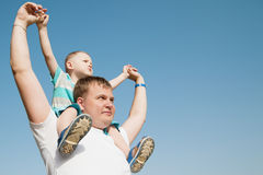 Son sits on father's shoulders. And they look to the side, against the blue sky stock images