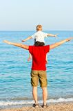 Son sits on his fathers shoulders his arms to the side. Against the sea royalty free stock photo