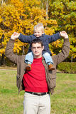 Son sits on shoulders at the father. Small son sits on shoulders at the father. Walk in autumn park in solar weather royalty free stock images