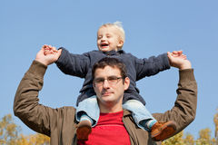 son sits on shoulders at the father Stock Image