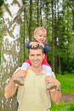 Son sits on shoulders at  father Stock Photo