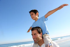Son sitting on father's shoulders on the beach. Father holding son on his shoulders at the beach Royalty Free Stock Photos