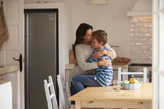 Son Sitting On Kitchen Table And Hugging Mother Stock Photo