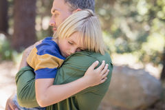 Son sleeping on fathers shoulder in forest Stock Image