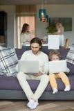Son som imiterar fadersammanträde på den hemmastadda hållande bärbara datorn för soffa Arkivbild