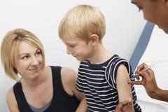 Son som injiceras av en kvinnlig doktor fotografering för bildbyråer