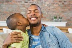 Son som kysser hans fader på soffan Arkivbild