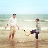 Son som spelar med en fotboll medan hans faderwatche Royaltyfri Foto