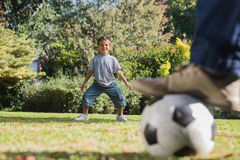 Son standing as goal keeper with dad. In the park stock images