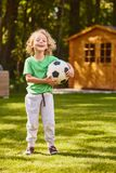 Son standing with a ball. Son standing in the garden with a football ball royalty free stock photo