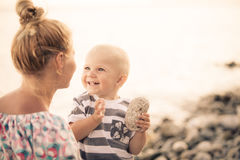 Son with stone in hand is smiling to his mother. On the walk Stock Photography