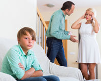 Son suffering of parents argue. Sad teenager son suffering of parents argue at home Stock Images