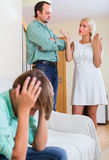 Son suffering of parents argue. Unhappy teenager son suffering of parents conflict at home Stock Photography