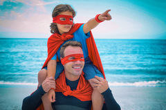 Son in superhero costume pointing while father carrying on shoulder Stock Image