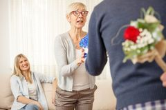 Son surprises his mother and sister with gifts royalty free stock image