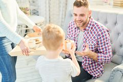 Son Surprising Dad with Present. Warm toned portrait of handsome young men looking fondly at his son giving him present and surprise breakfast for Fathers day at royalty free stock photos