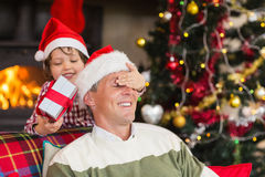 Son surprising his father with christmas gift. At home in the living room stock photo
