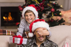 Son surprising his father with christmas gift. At home in the living room stock image