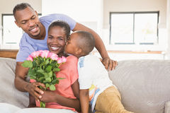 Son surprising mother with flowers. In living room Royalty Free Stock Photography