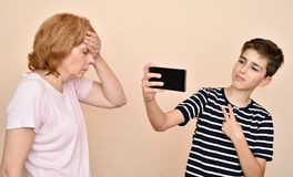 Son taking selfie while his mother is slapping her head with hand stock image