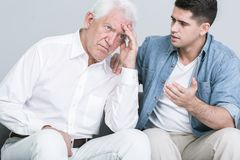 Son talking with worried father. Young handsome men talking with worried father Stock Photos