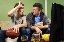 Son teasing his father holding loser sign. While watching football on television Stock Photos