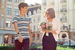 Son is teenager walking with his mother outdoor, mom holding bouquet of flowers gift from her son on mother`s day royalty free stock photography