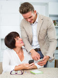 Son telling elderly mother how to use phone Royalty Free Stock Images