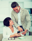 Son telling mother how to use phone. Son telling his mother how to use phone Royalty Free Stock Images