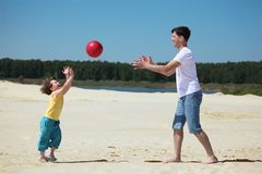 Son throws  ball to father on sand. Summer day Royalty Free Stock Photos
