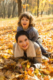 Son on top her mother in autumn park Royalty Free Stock Images