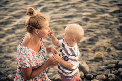 Son touches my mother`s nose at the seashore. Mother and son spending time together on the shore of the beach. Boy touch the nose, happy women laughing Stock Photo