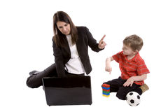 Son trying to play mom working. Mom is pointing to her son to wait while she works Royalty Free Stock Photos