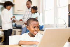 Son using laptop in the kitchen. Son using laptop against parents in the kitchen stock photos